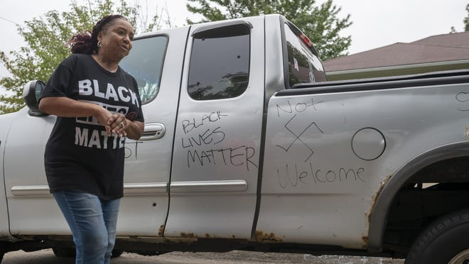 Candace Hall stands in front of graffiti written on her truck in front of her Warren home, September 10, 2020. In an attack on the home Wednesday evening, a large rock was thrown through the window, racial threats were written on their car and several tires were slashed.