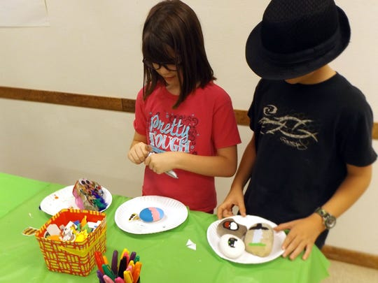 Local children paint rocks during the Alamogordo Public Library's last rock painting party.