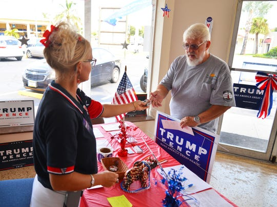 Jeff White of Cape Canaveral stops by a Donald Trump office in Cocoa Beach to pick up signs and other gear. Volunteers are busy preparing for the presidential candidate's visit to Melbourne.