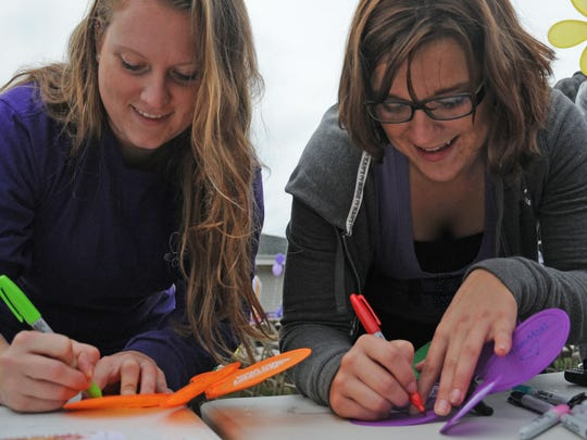 Emily Rey, left, and Amanda Jones write on their memory flowers on during the 2012 Walk to End Alzheimer's. The walk featured 67 teams and approximately 550 walkers.