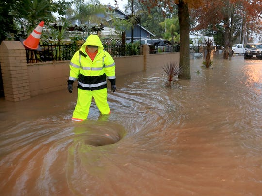 Scott Taylor of Windsor Public Works opens a manhole to help drainage along Old Redwood Highway in Windsor, Calif. during flooding Thursday, Dec. 11, 2014. A powerful storm churned down the West Coast Thursday, bringing strong gales and much-needed rain and snow. (AP Photo/Santa Rosa Press Democrat, Kent Porter)