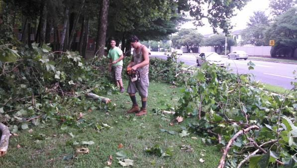 Justin Messick, left, and Riah Hobson clean up debris on Beaglin Park Drive in Salisbury after Thursday's storm.