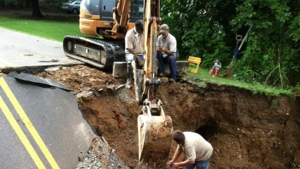 A crew works in a area where floodwaters damaged East University Parkway today.