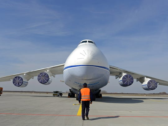 A crew member walks in front of the airplane during the 30th anniversary of the maiden flight of the world's largest serially manufactured cargo airplane Antonov An124 Ruslan in Leipzig, central Germany, Monday, April 8, 2013.