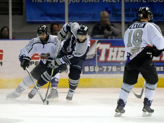 Knoxville Icebears' Jarrett Rush (left) and Ice Flyers' Brett Lutes go after the puck during second period action Sunday at the Pensacola Bay Center.
