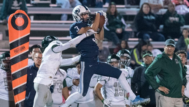Central Valley Christian's Gavin Salierno pulls down a pass under pressure from Dinuba's Israel Garcia in a Central Sequoia League football game on Friday, October 28, 2016.