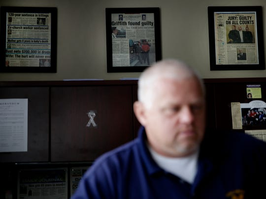 Framed newspaper articles of major cases hang on the walls of Johnson County Prosecutor Brad Cooper's office June 7, 2016.