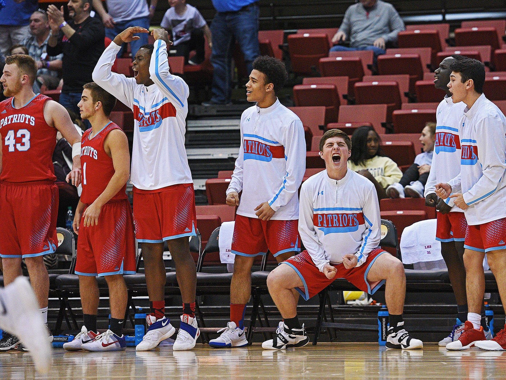 Lincoln players react from the bench after a teammate scored during a 2017 SDHSAA Class AA State Boys Basketball quarterfinal game against Huron Thursday, March 16, 2017, at Rushmore Plaza Civic Center in Rapid City. Lincoln beat Huron 56-47 in overtime.