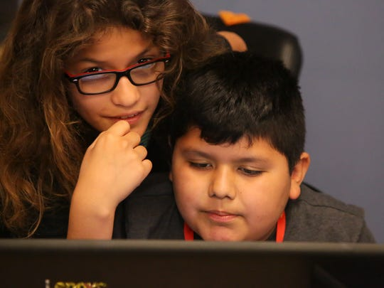 Isaac Noriega, left, helps his brother, David, during a coding summer camp program at College of the Desert, Thursday, June 29, 2017.