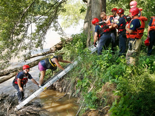 Members of the Tippecanoe County Sheriff's Office and the Lafayette Fire Department rescue three women from the waters of Wildcat Creek Friday, July 21, 2017, off County Road 50 N near Wildcat Valley Estates. The women were part of a group of eight women rafting on the creek.