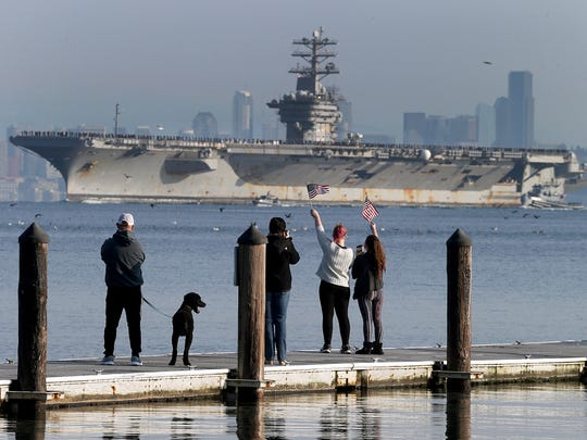 The USS Nimitz returns from a a deployment that began in June, people greet and photograph the ship from the Manchester Pier on Sunday.