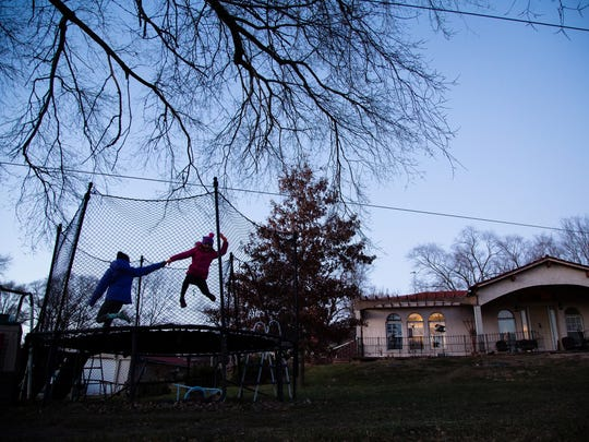 Sisters, Sadi Magnuson, 10, left, and Mayci, 8, right, play on a trampoline in their grandparents front yard on Wednesday, Dec. 6, 2017, in Carbon. The girls and their two other siblings are the only children left in Carbon.