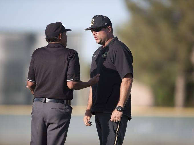 Basha head coach Jim Schilling talks with an umpire