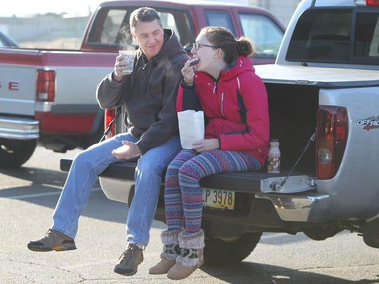 """Steve Hensley has a cup of coffee and his daughter Alexandra, 16, a donuts, as they sit on the tailgate of his pickup truck outside Mimi's Donuts and Bakery,  Millville.  The business is one of nine independent donut shops on the Butler County """"Donut Trail."""" The Enquirer/Patrick Reddy"""