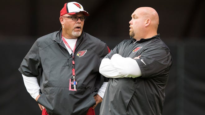 Cardinals head coach Bruce Arians (left) and General Manager Steve Keim talk during training camp at University of Phoenix Stadium on July 29, 2014.
