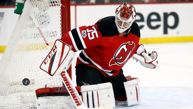 New Jersey Devils goalie Cory Schneider deflects a shot by the Ottawa Senators during the first period of an NHL hockey game, Tuesday, Feb. 21, 2017, in Newark, N.J. (AP Photo/Julio Cortez)