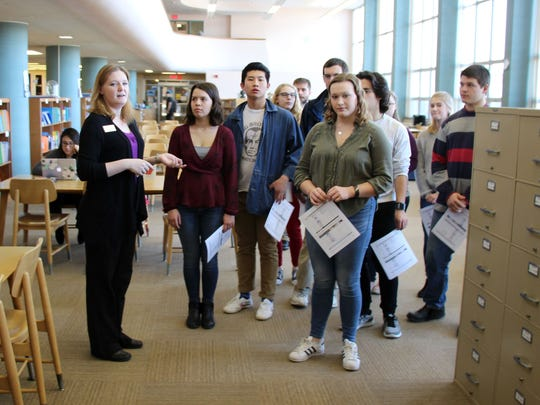 Natalie Long, director of library services at Silver Lake College, familiarizes Roncalli High School students with resources available to them as participants in a dual-credit theology course