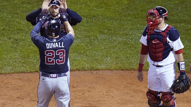 Atlanta Braves' Adam Duvall (23) is congratulated by Travis d'Arnaud, after his second home run of the game during the sixth inning of a baseball game, against the Boston Red Sox, Wednesday Sept. 2, 2020, in Boston. At right is Boston Red Sox catcher Kevin Plawecki.