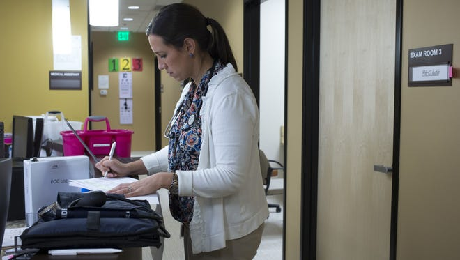Katie Krahe, a physician assistant, fills out paperwork after seeing a patient on Dec. 16, 2014, at the Mesa Health & Wellness office.