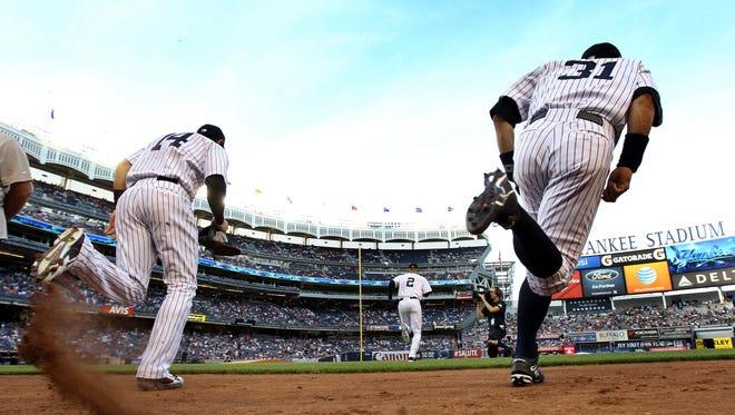 Shortstop Derek Jeter leads second baseman Brian Roberts (14) and right fielder Ichiro Suzuki (31) onto the field at Yankee Stadium Friday night.