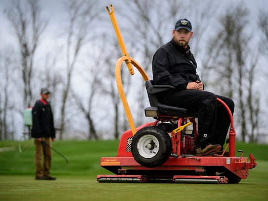 Jonathan Graham uses a Tru-Turf Roller to smooth out the Hole 12 green at Victoria National Golf Course in Newburgh, Ind., Tuesday, April 24, 2018.