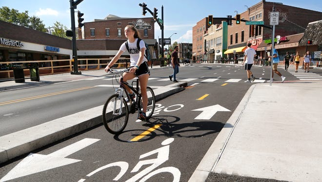 A cyclist pedals east on the new State Street bike lane Monday, September 25, 2017, in the Chauncey Village in West Lafayette.