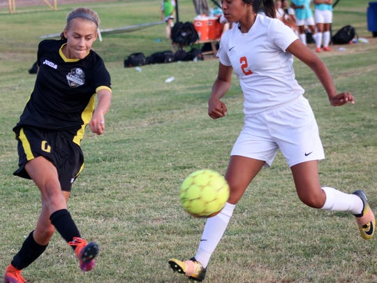 Alamogordo's Sheyenne Drake, left, passes a ball while being defended by Artesia's Destiny Gonzales.