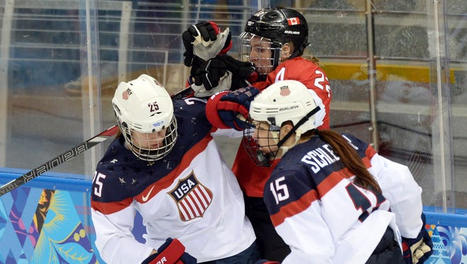 USA defenseman Anne Schleper (15) and forward Alex Carpenter (25) combine to hit Canada forward Hayley Wickenheiser (22) in their game Wednesday at the Sochi Olympics.