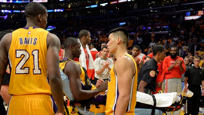 Lakers forward Julius Randle is greeted by teammates as he is carted off the Staples Center floor during Tuesday's game.