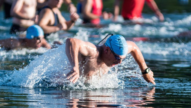 The Sprint Triathlon in Denville starts with athletes diving into Cook's Pond .