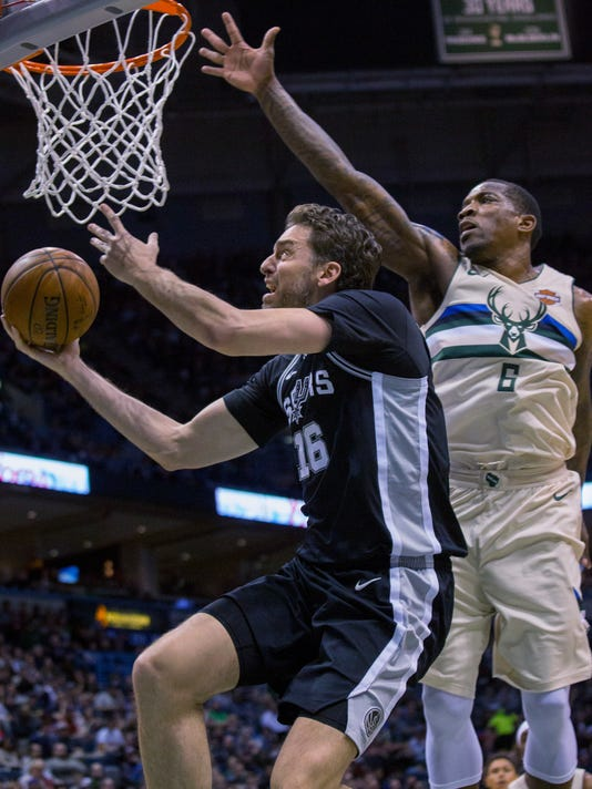 San Antonio Spurs center Pau Gasol, left, goes up for a basket against Milwaukee Bucks guard Eric Bledsoe, right, during the second half of an NBA basketball game Sunday, March 25, 2018, in Milwaukee. (AP Photo/Darren Hauck)