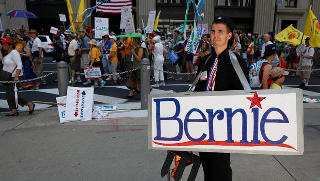 Josh Lechner of Pittsburgh carries a sign in support of Sen. Bernie Sanders, I-Vt., as he marches during a protest in downtown on Sunday, July 24, 2016, in Philadelphia.