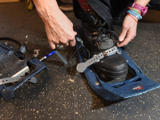 Cindy Dunbar demonstrates how to put on snowshoes on