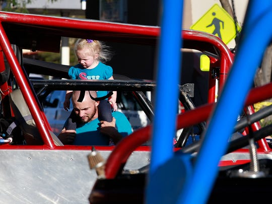 Jacob Bean and his daughter, Aliyah Bean, 2, take in last year's Fall Crawl on Main Street in downtown Farmington.
