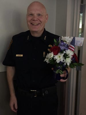 """Farmington Hills Assistant Police Chief Matt Koehn holds a bouquet with a card that reads """"Blue Lives Matter."""" The Farmington Public Safety Department received one, too."""