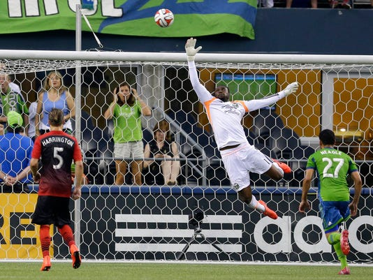 Portland Timbers goalkeeper Donovan Ricketts, center, leaps for a shot that went over the net as Seattle Sounders' Lamar Neagle, right, and Timbers' Michael Harrington (5) look on in the first half of an MLS soccer match, Sunday, July 13, 2014, in Seattle. (AP Photo/Ted S. Warren)