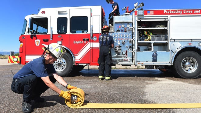 Craig LoSasso, division chief of operations and training at Wellington Fire Protection District, rolls up a hose after a training exercise in Wellington in this file photograph.
