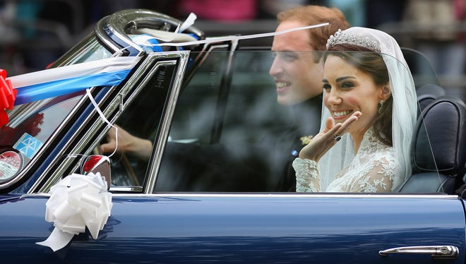 Prince William, Duke of Cambridge and Catherine, Duchess of Cambridge drive from Buckingham Palace in a decorated sports car on April 29, 2011 in London, England. The marriage of the second in line to the British throne was led by the Archbishop of Canterbury and was attended by 1900 guests, including foreign Royal family members and heads of state. Thousands of well-wishers from around the world have also flocked to London to witness the spectacle and pageantry of the Royal Wedding.   (Photo by Jeff J Mitchell/Getty Images) ORIG FILE ID: 113270944