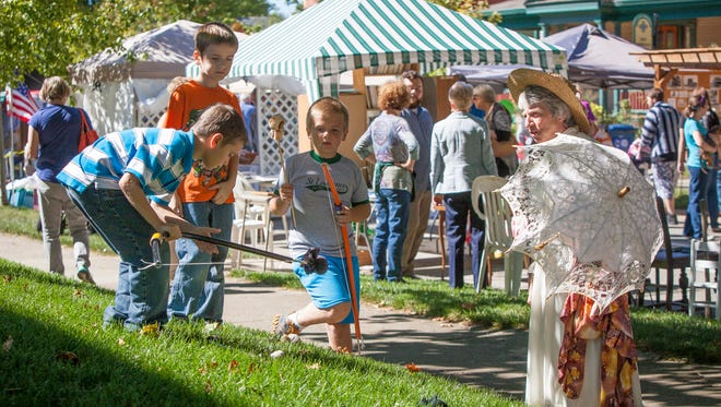 Lynn Thornburg talks to her great-grandnephews as they and other children play in the yard during the Old Washington Street Festival in 2015.