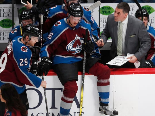 Colorado Avalanche coach Jared Bednar, right, confers with right wing Mikko Rantanen, center, and center Nathan MacKinnon after drawing up a play during a timeout in the third period of an NHL hockey game against the Philadelphia Flyers on Wednesday, March 28, 2018, in Denver. Philadelphia won 2-1. (AP Photo/David Zalubowski)