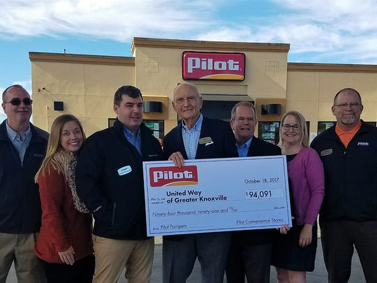 "Pilot founder and chairman James Haslam II, center, presents a check for $94,091 to United Way of Greater Knoxville CEO Ben Landers, third from right. The money came from Pilot Flying J's annual ""Pilot Celebrity Pumpers"" fundraiser."