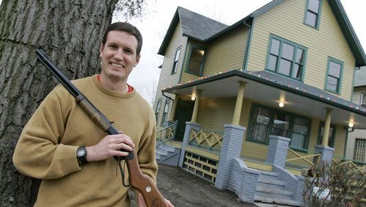 Brian Jones poses with his Red Ryder air rifle outside the renovated home which was used in the classic movie 'A Christmas Story' in Cleveland, Monday, Nov. 13, 2006. He now has the real Red Ryder.
