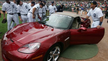 Detroit Tiger players check  out the new red Chevrolet Corvette given to Armando Galarraga by General Motors before a Detroit Tigers  game in 2010