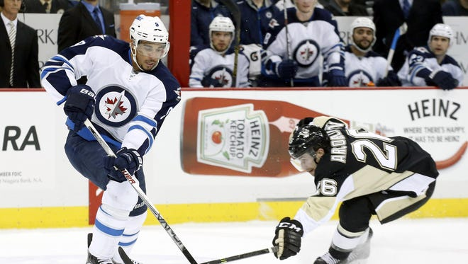 Evander Kane, left, handles the puck during a game against the Pittsburgh Penguins last month.