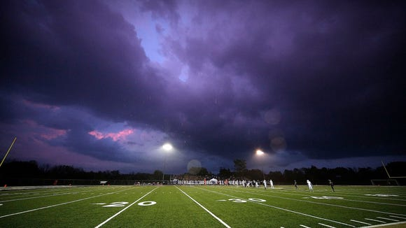 A rain squall blows across the field during the first quarter of the Franklin versus Oak Creek varsity football game at Franklin High School Friday, Sept. 16, 2016, in Franklin, Wisconsin.