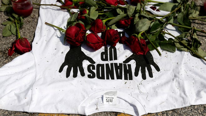 """A shirt reading """"hands up don't shoot,"""" at the spot Michael Brown was killed."""