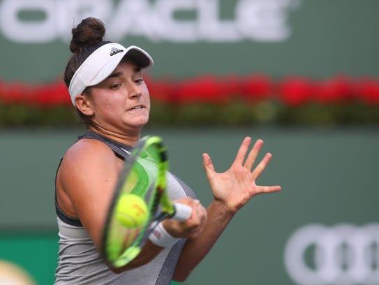 American Caroline Dolehide returns the ball to Simona