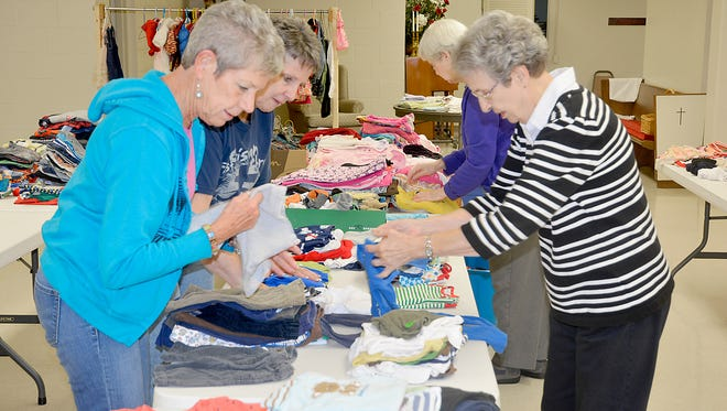 First Christian Church in Henderson, at 830 S. Green Street, is holding a clothing giveaway on Saturday.  The event runs from 9 a.m. to 1 p.m.  Anyone is welcome to come and take part.  In this photo, members of the church organize the items earlier this week.