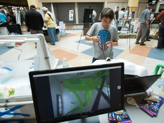 "Brayden Allison, 9, tries to complete a ""surgery"" using tools similar to those used in laparoscopic surgery at the New Mexico Space Museum booth on the second day of the Las Cruces Space Festival at the Mesilla Valley Mall, Friday April 13, 2018. Dave Dooling, the education director from the museum, said that after a person participates in the surgery activity, he discusses how those skills could be utilized by a robot."