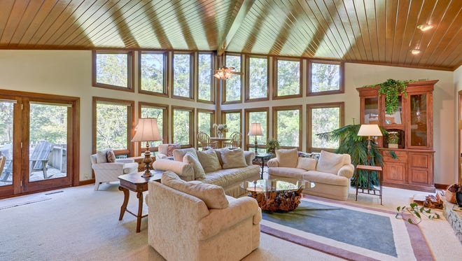 The great room features a vaulted wood-paneled ceiling and an impressive wall of windows overlooking the lake. Doors to the left lead out to the wrap-around deck.